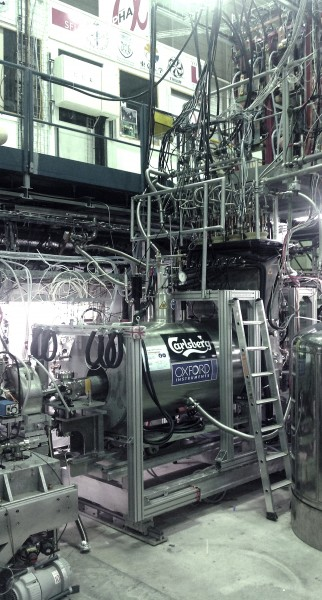 A view from the Experimental Zone floor of the ALPHA-2 Cryostat and external solenoid assembly, with control and data acquisition electronics located on the overhead platform above the cryostat. Photo by Robert Thompson, ALPHA-2 member, University of Calgary