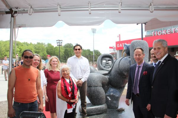 Ahqahizu, a monumental sculpture of an Inuit soccer player embellished with silver eyes and holding a bronze walrus skull for a ball was unveiled today at York Lions Stadium. From left, Inuit sculptor Ruben Komangapik; project lead and York U Professor Anna Hudson; Rhonda Lenton, Vice-President and Academic Provost; Native women's rights activist Jeannette Corbiere; Inuit artist Koomuatuk (Kuzy) Curley; Shawn Brixey, Dean, School of Arts, Media Performance & Design (AMPD); Gary Brewer Vice-President, Finance and Administration (partially seen); and Mamdouh Shoukri, President and Vice-Chancellor, York University
