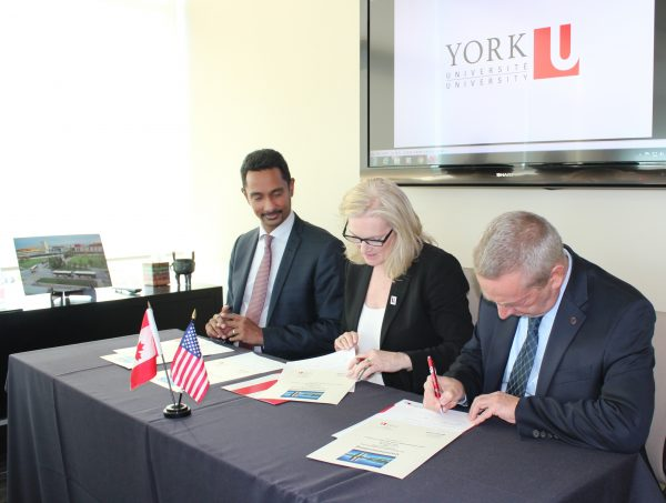 image of York U Faculty of Science Dean, York U President and Director of Fermilab Nigel Lockyer signing an MOU