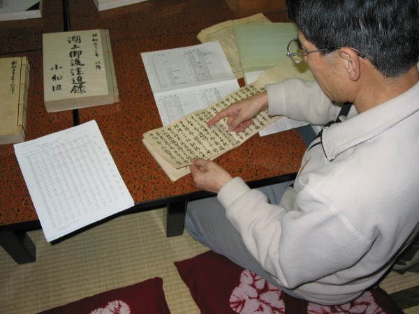 The Priest Mr. Kiyoshi Miyasaki pointing out some of the records on lake ice and the omiwatari. His data sheet summarizing the records are on the table. Photo taken Nov 3, 2005 by JJMagnuson.