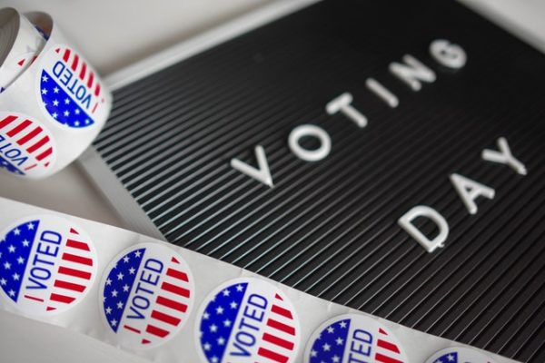 Image of ballots and voting day message